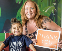 Mother and boy patient holding Thank You sign