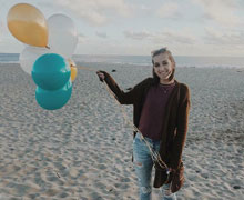 Camille in the beach with balloons