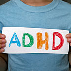 Kid in blue T shirt holding a sign that says ADHD in crayon