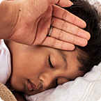 Parent feeling sleeping childs forehead