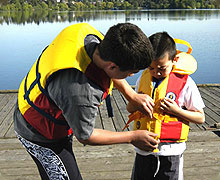 Parent helping child with life jacket