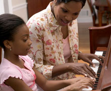 Mom and child playing piano