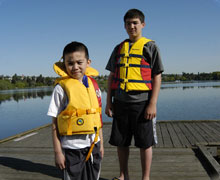 Kiddos standing on a dock with life jackets on
