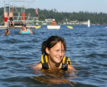 Teen swimming in water with life jacket on